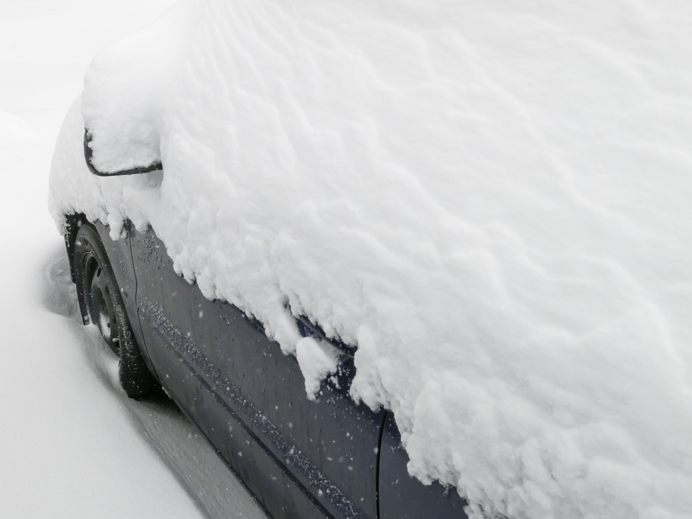 Winter at a glance Top of car buried in snow during a storm