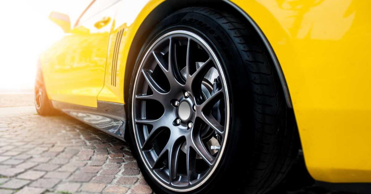 yellow sports car close up of shiny clean wheel and road